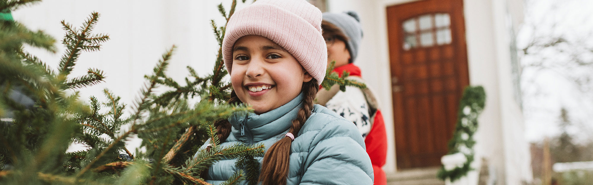 Girl outdoors carrying a christmas tree.